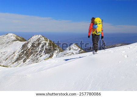 Backpacker descending a snowy mountain in sunny day of the winter - stock photo