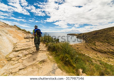 Backpacker exploring the inca's majestic footpaths on Island of the Sun, Titicaca Lake, among the most scenic travel destination in Bolivia. Travel adventures and vacations in the Americas.