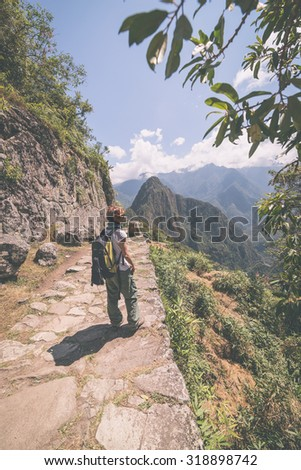 Backpacker exploring the steep Inca's footpaths of Machu Picchu, the most visited travel destination in Peru. Summer adventures in South America, marsala toned image. - stock photo