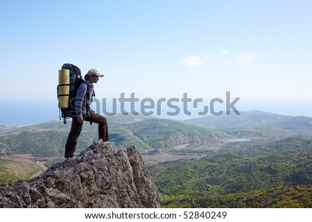 Backpacker girl standing on a high cliff over sea - stock photo