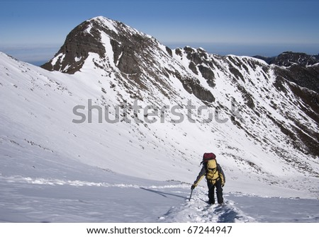Backpacker in winter mountain with beautiful scenery.