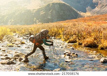 Backpacker jump across the mountain river using sticks - stock photo