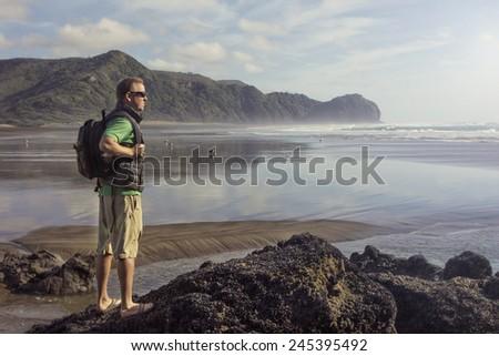 Backpacker looking at beautiful ocean view - stock photo