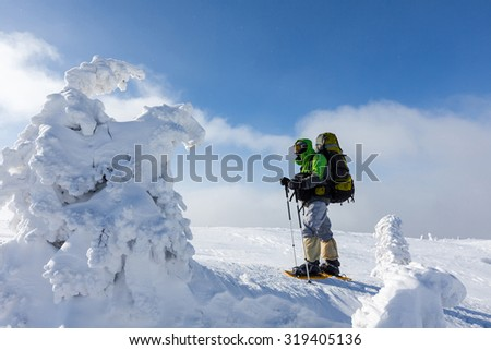 Backpacker man walking in winter mountains on sunny day