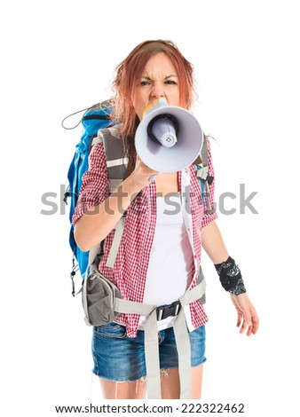 backpacker shouting by megaphone over white background - stock photo