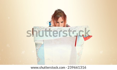 backpacker showing map over ocher background - stock photo