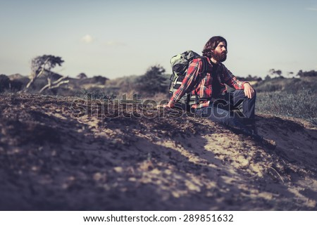 Backpacker taking an evening break sitting on a sandy dune covered in low scrub looking thoughtfully towards the setting sun - stock photo
