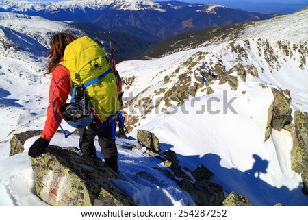 Backpacker traversing mixed terrain in sunny winter day