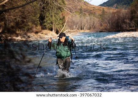 Backpacker wade rugged mountain river