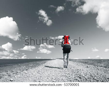 Backpacker walking on gravel road under sky with clouds