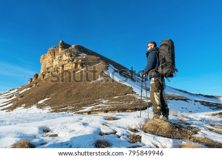 Backpacker with a large backpack and sticks ascends to the rock on sunset against the background of epic rocks in the winter season.