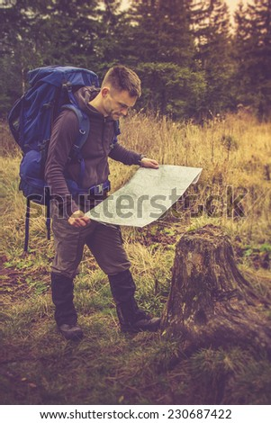 Backpacker with map to find directions in wilderness area.Filtered image:cross processed vintage effect. - stock photo