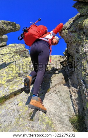 Backpacker woman descending a steep gully on the mountain - stock photo
