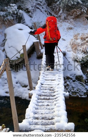 Backpacker woman traversing a mountain river on snow covered bridge - stock photo