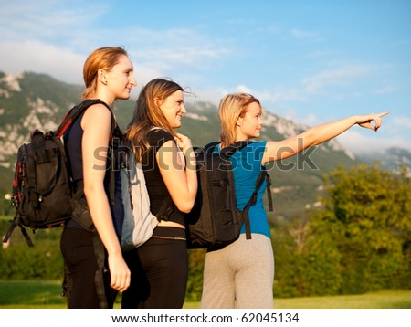 Backpackers on travel - Group of three cute young girls with backpacks on a trip across grass field - stock photo