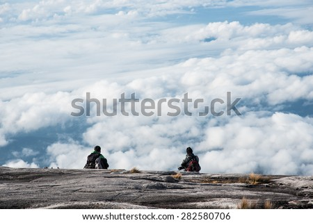 Backpackers talking on the cliff over the cloud - stock photo
