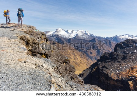 Backpackers tourists traveling standing walking hiking people walking mountain trail edge, El Choro trek, Cordillera real mountains canyon valley range ridge, Bolivia tourism.