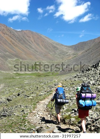Backpackers trekking on siberian high mountain