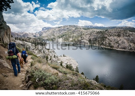 Backpackers with dog hiking near mountain lake. - stock photo