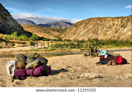 Backpacks lying next to awesome river in mountains. Shot in the Langeberge highlands near Grootrivier and Gouritsrivier rivers crossing, Garden Route, Western Cape, South Africa. - stock photo