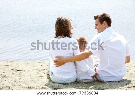 Backs of happy family sitting on sandy shore in front of blue water - stock photo