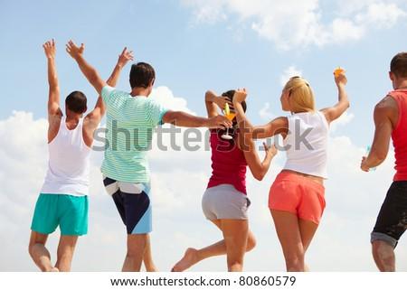 Backs of happy young friends dancing at beach party - stock photo