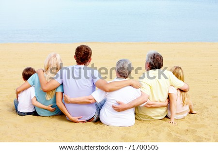 Backs of serene family members sitting on sandy shore in front of blue water - stock photo