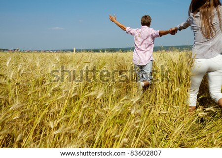 Backs of woman and man holding by hands while running in the field - stock photo