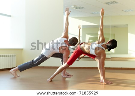 Backs of young sporty girl and guy doing physical exercise in gym - stock photo