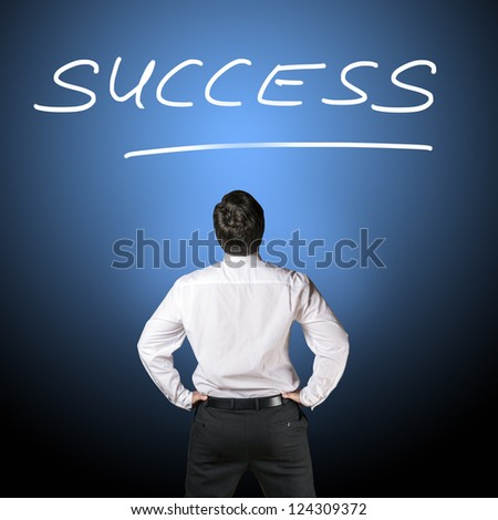 """Backside of a business man in black business trousers and white business shirt who is looking to lettering """"success"""" with a blue-black background - stock photo"""