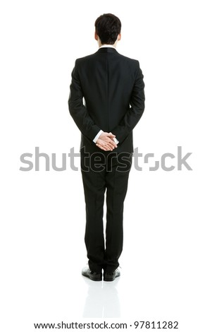 Backside of a businessman in a black suit, taken on white background. - stock photo