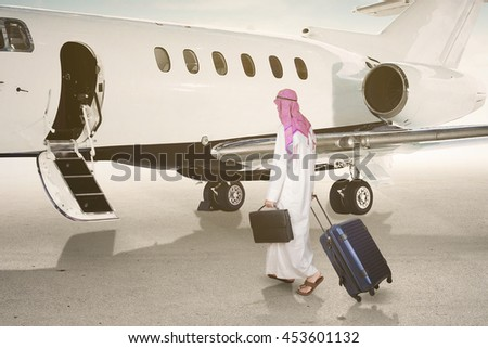 Backside of Arabic businessman walking towards corporate jet while carrying suitcase - stock photo