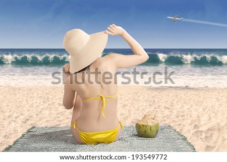 Backside of sexy girl sitting on beach looking at airplane - stock photo