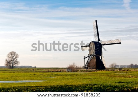 """Backside of the windmill """"Zandwijkse Molen"""" dated from 1699 in the Dutch village of Sleeuwijk (municipality of Woudrichem, province of North Brabant). This mill is no longer in use as a polder mill. - stock photo"""