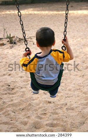 Backside of toddler boy on a swing at the park. - stock photo