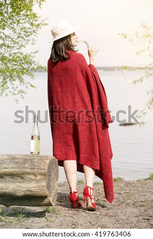 backside of woman wrapped in red blanket standing by the water and holding a glass of champagne