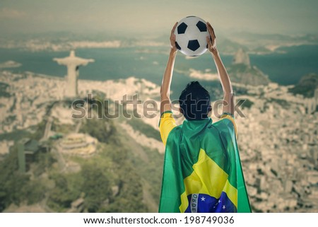 Backside of young man with a Brazilian flag on his back while holding a ball celebrate winning - stock photo