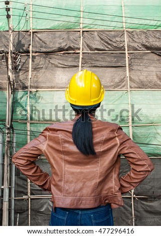 backside woman engineer contractor cloth yellow helmet with under construction background