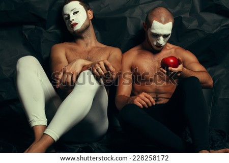 Backstage concept. Arty portrait of two circus performers in tights holding red apple, posing over black cloth. White masks on faces. Muscular bodies and perfect tan. Halloween party - stock photo