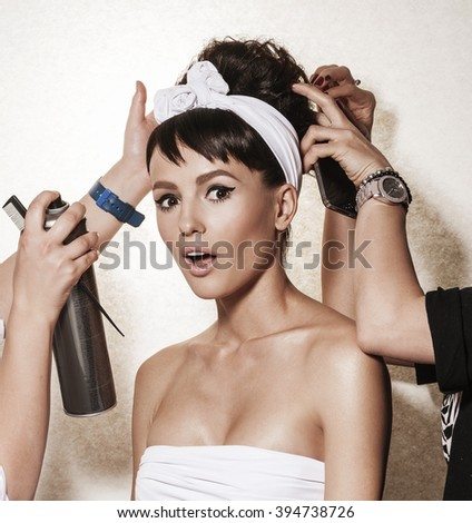 Backstage photo bridal rituals before wedding. Beautiful brunette woman with retro hairdo and makeup. Luxury vogue style model posing in studio. Bridal makeup and wedding ideas concept. - stock photo