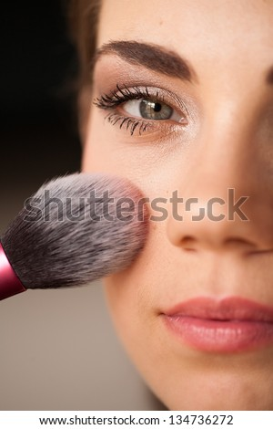 Backstage scene: Professional Make-up artist applying blusher - stock photo