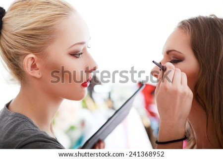 Backstage scene: Professional Make-up artist doing glamour model makeup at work - stock photo