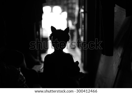 Backstage theater; silhouette of a child actor in cat ears handband  - stock photo