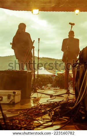 backstageof an aoutdoor concert with two performers and lots of cables  - stock photo