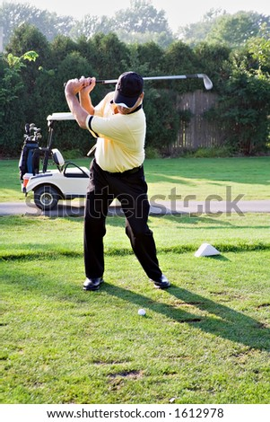 Backswing at the first tee. - stock photo