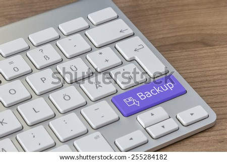 Backup and disk symbol on a large blue button of a modern keyboard on a wooden desktop - stock photo