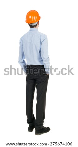 Backview of an engineer in construction helmet stands. man in trousers and shirt standing at a construction site holding hand helmet. Engineer in a helmet stands with his hands in his pockets - stock photo