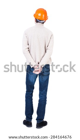 Backview of an engineer in construction helmet stands. Standing young guy. Rear view people collection. .  Isolated over white background. Engineer in a warm jacket is hands clasped behind his back. - stock photo