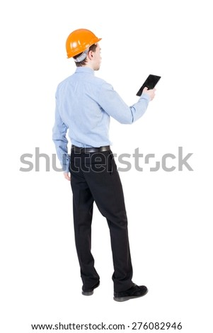 Backview of business man in construction helmet stands and enjoys tablet or using a mobile phone. S backside view of person.  Isolated over white background. Businessman supervises construction. - stock photo