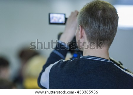 Backview of Professional Cameraman Filming Using Professional Videocamera. Horizontal Image - stock photo